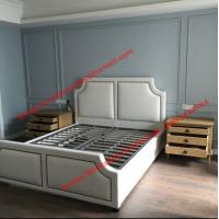 White fabric bed with copper nail decoration and slat wood support in black
